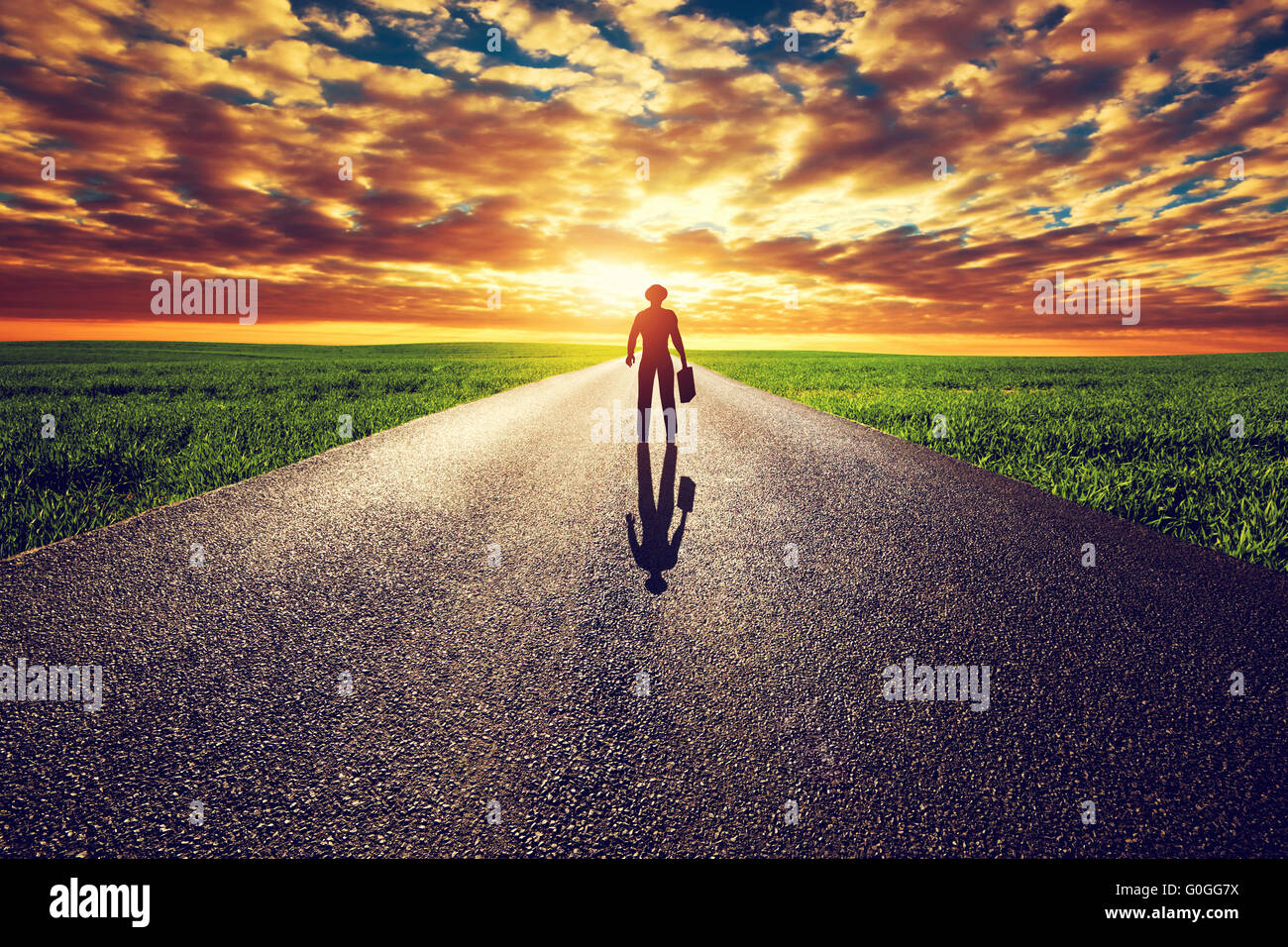 Man with suitcase and hat on long straight road towards sunset sky. Travel - Stock Image