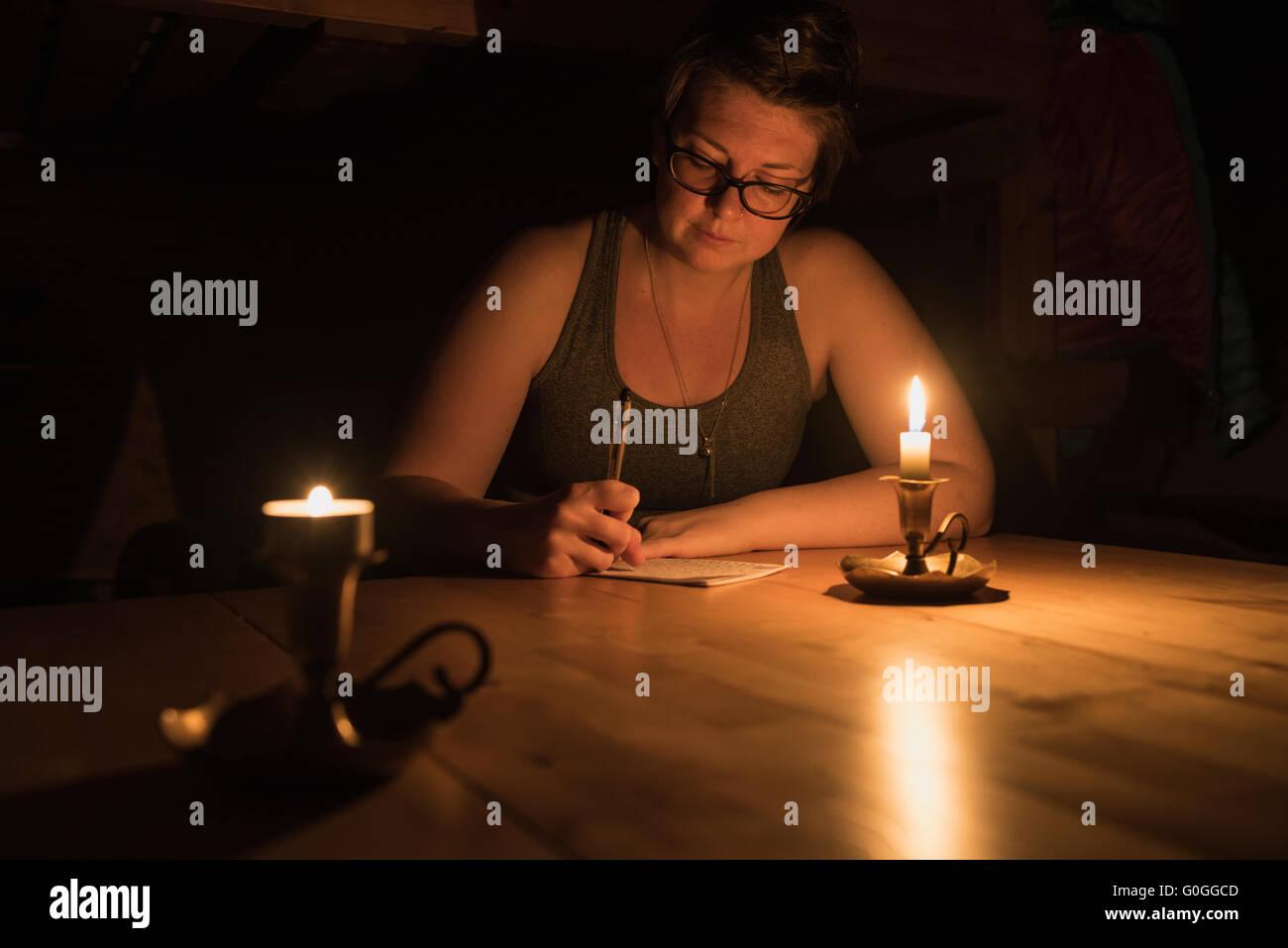 Female hiker writes in journal by candlelight at Abiskojaure hut, Kungsleden trail, Lapland, Sweden - Stock Image