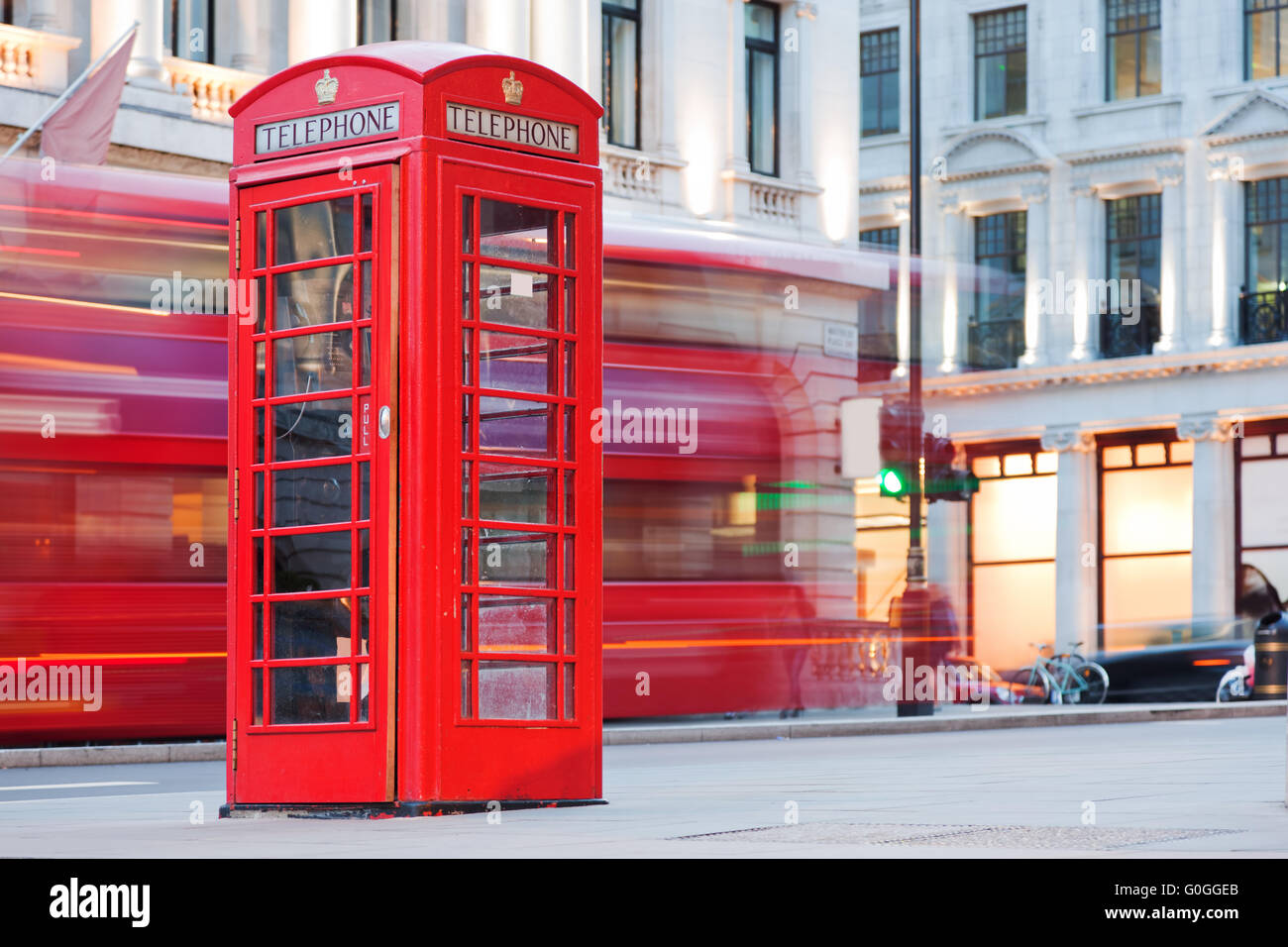 London, UK. Red telephone booth and red bus passing. Symbols of England. - Stock Image