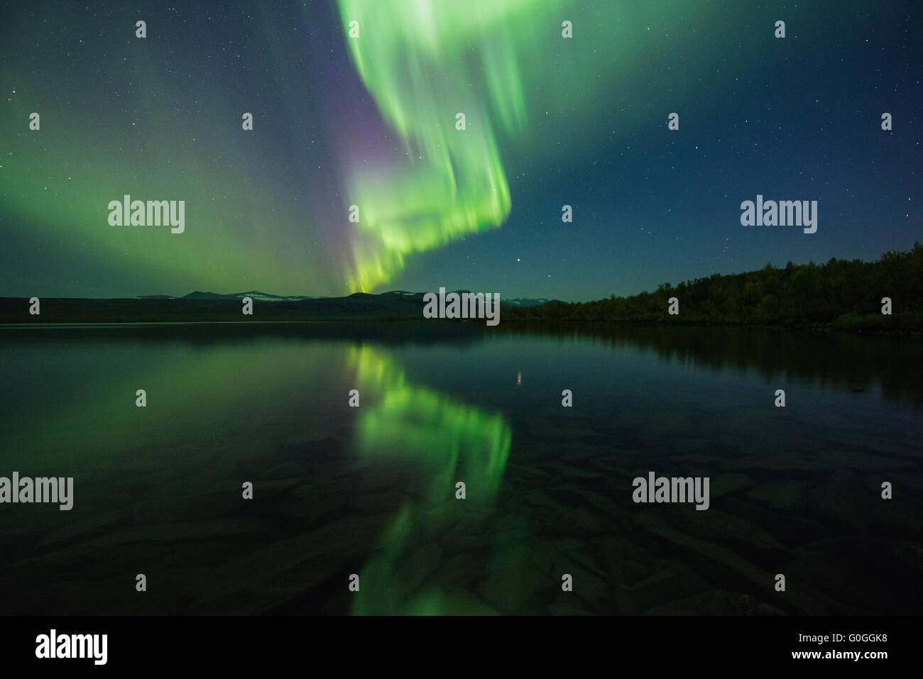 Northern lights reflect in lake Sitojaure outside of Sitojaure hut, Kungsleden trail, Lapland, Sweden - Stock Image