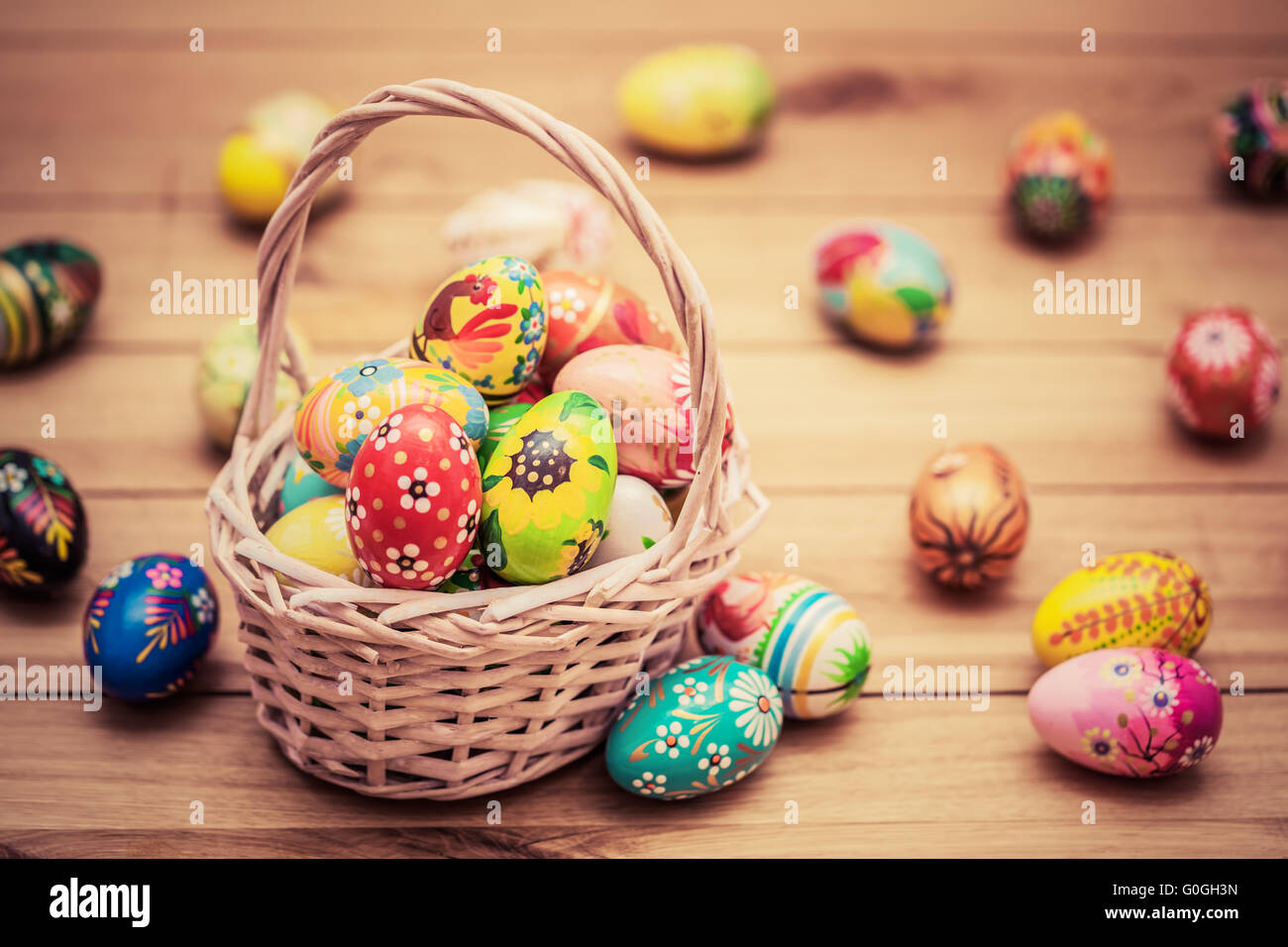 Colorful hand painted Easter eggs in basket and on wood. Handmade vintage decoration - Stock Image