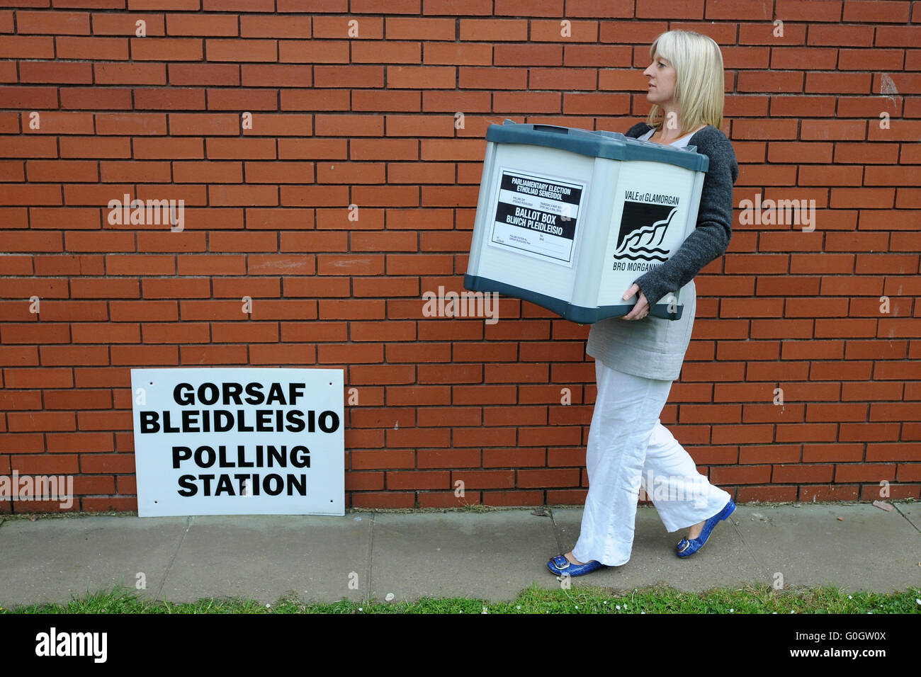 A council worker carries ballot boxes full of votes during the general election count in Barry, south Wales. - Stock Image