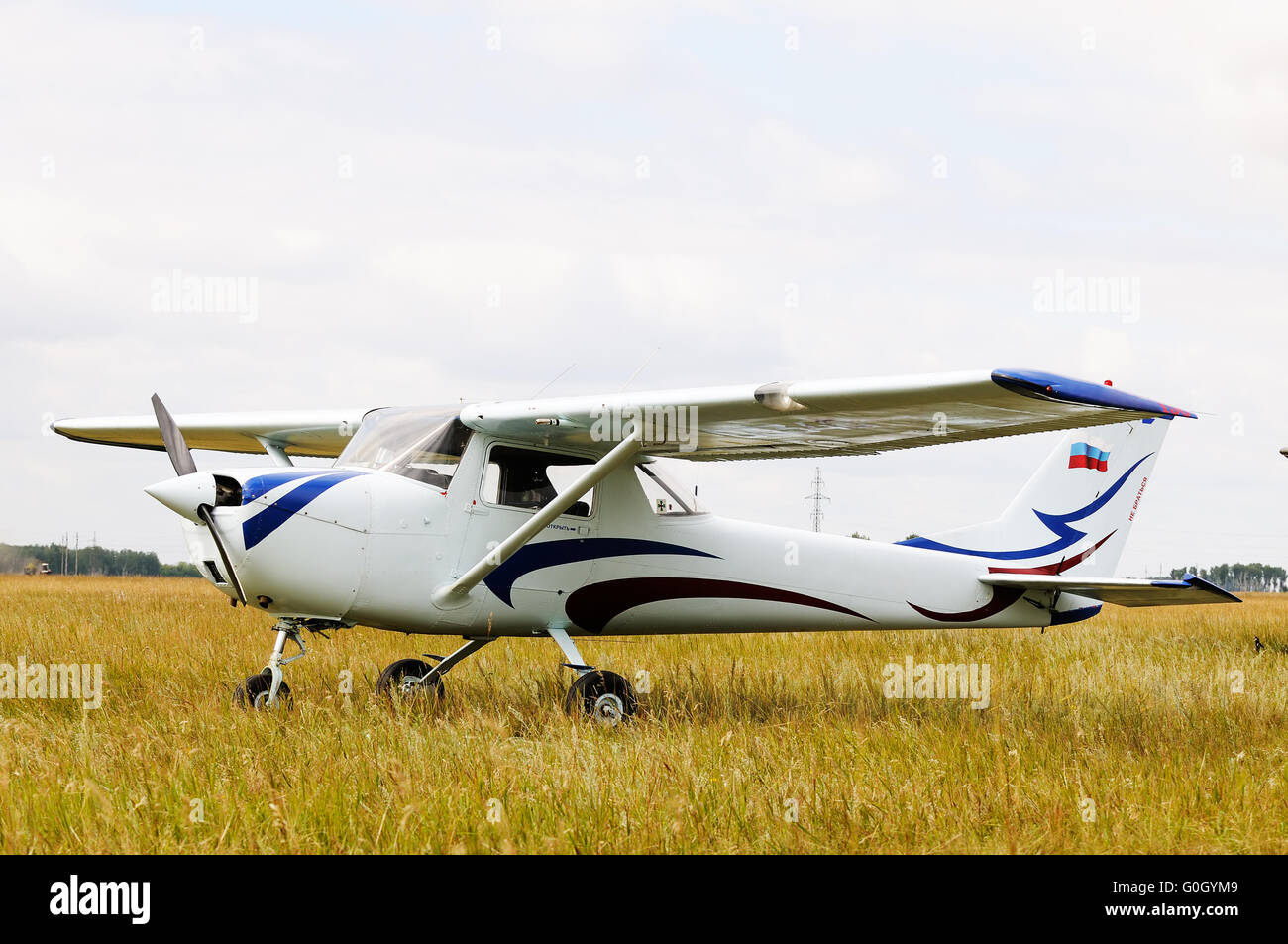 Private propeller-driven airplane landed in green field - Stock Image