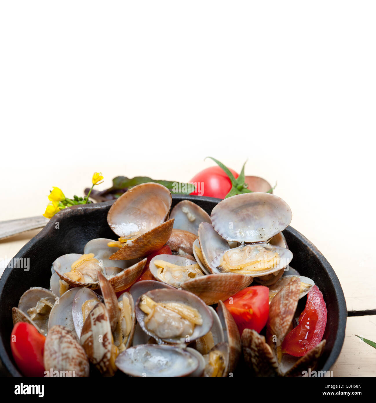fresh clams on an iron skillet - Stock Image