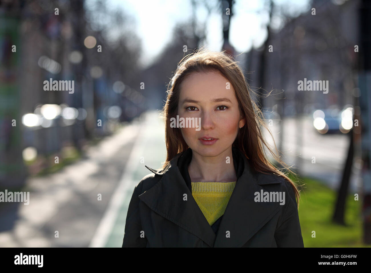Beautiful Asian woman with yellow sweater and olive coat walking on the street - Stock Image