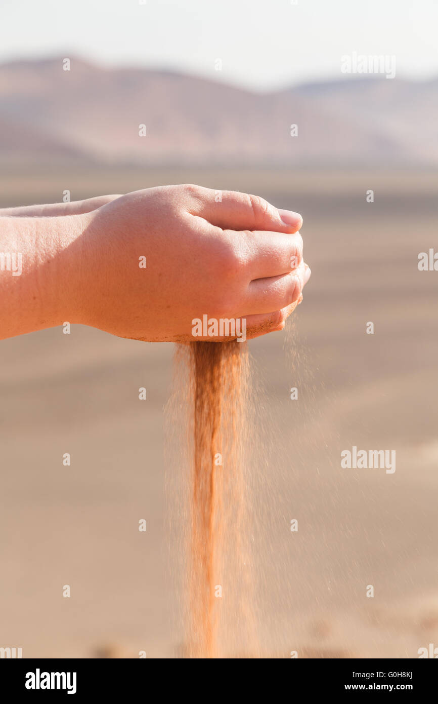 Sand running through hands. Time running out. - Stock Image