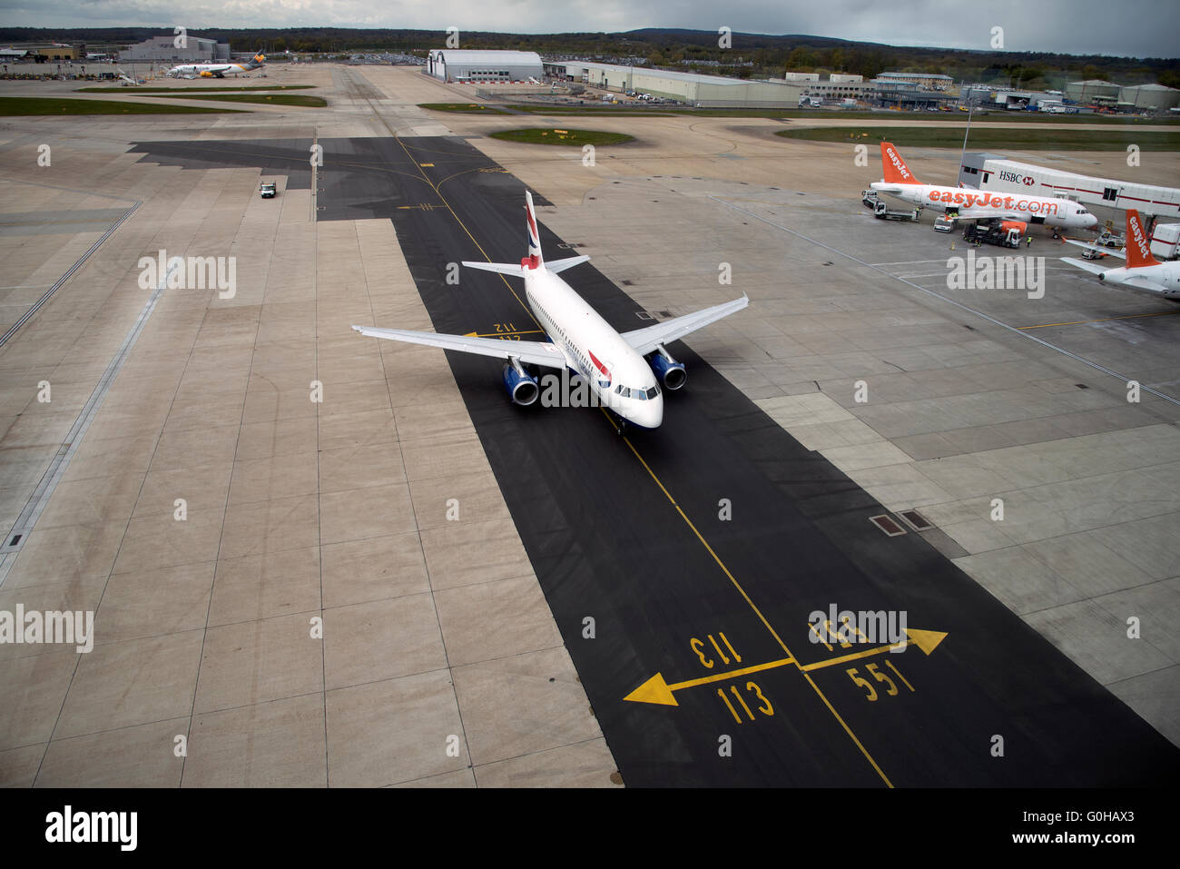 A British Airways passenger jet using a new tarmac taxiway at London Gatwick airport south of London England UK - Stock Image