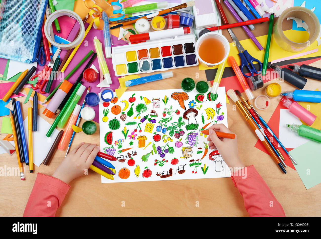 cartoon food collection, fruit and vegetables child drawing, top view hands with pencil painting picture on paper, - Stock Image