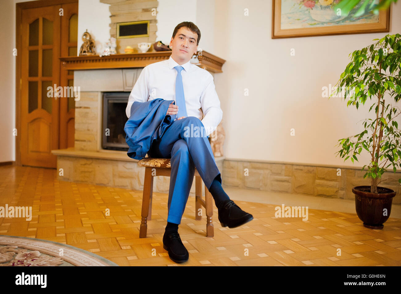 groom  gets dressed in formal wear and blue suit - Stock Image