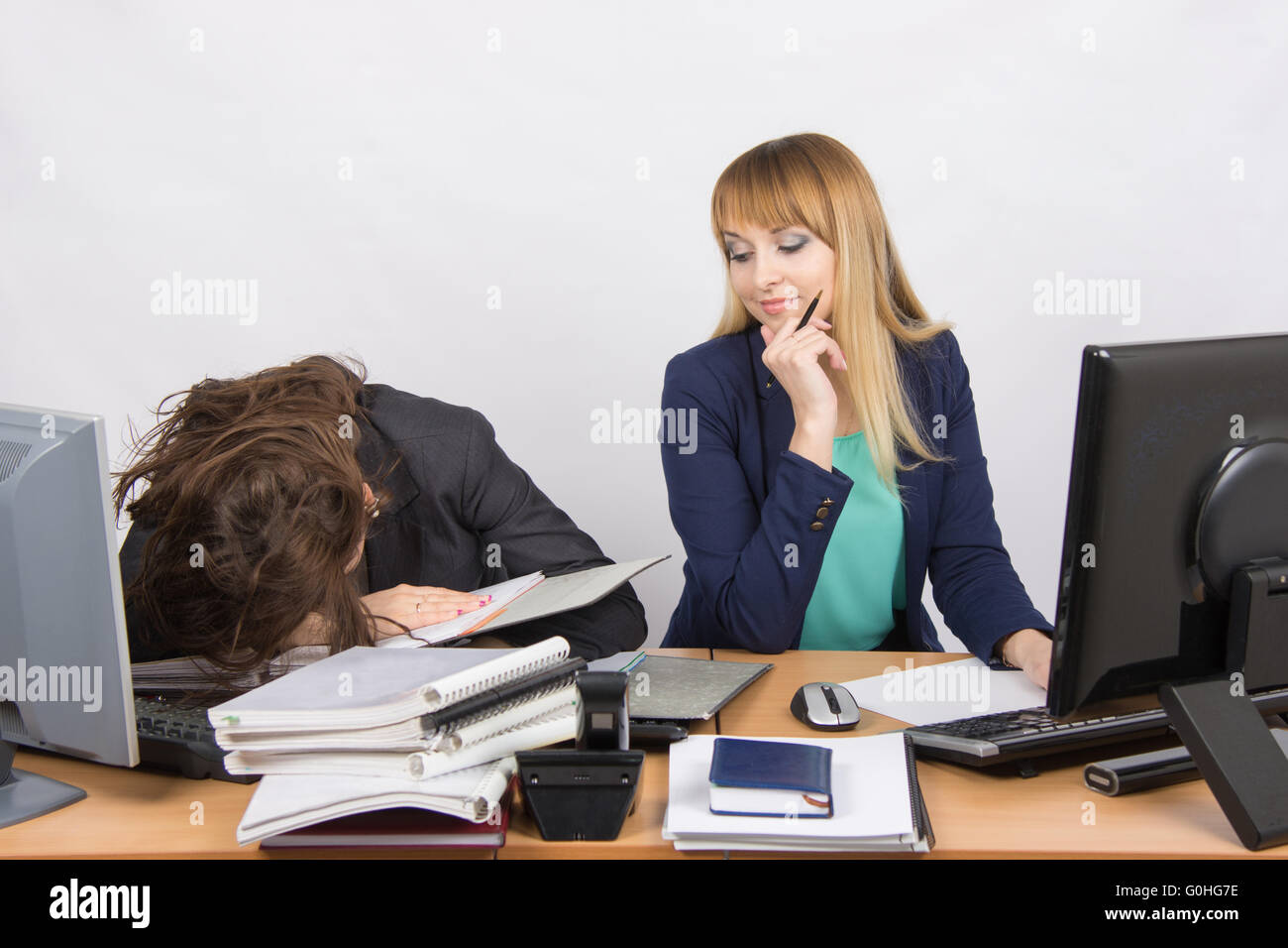 Female colleagues in the office, one had fallen asleep on a pile of folders, the second with a sneer looks at her - Stock Image