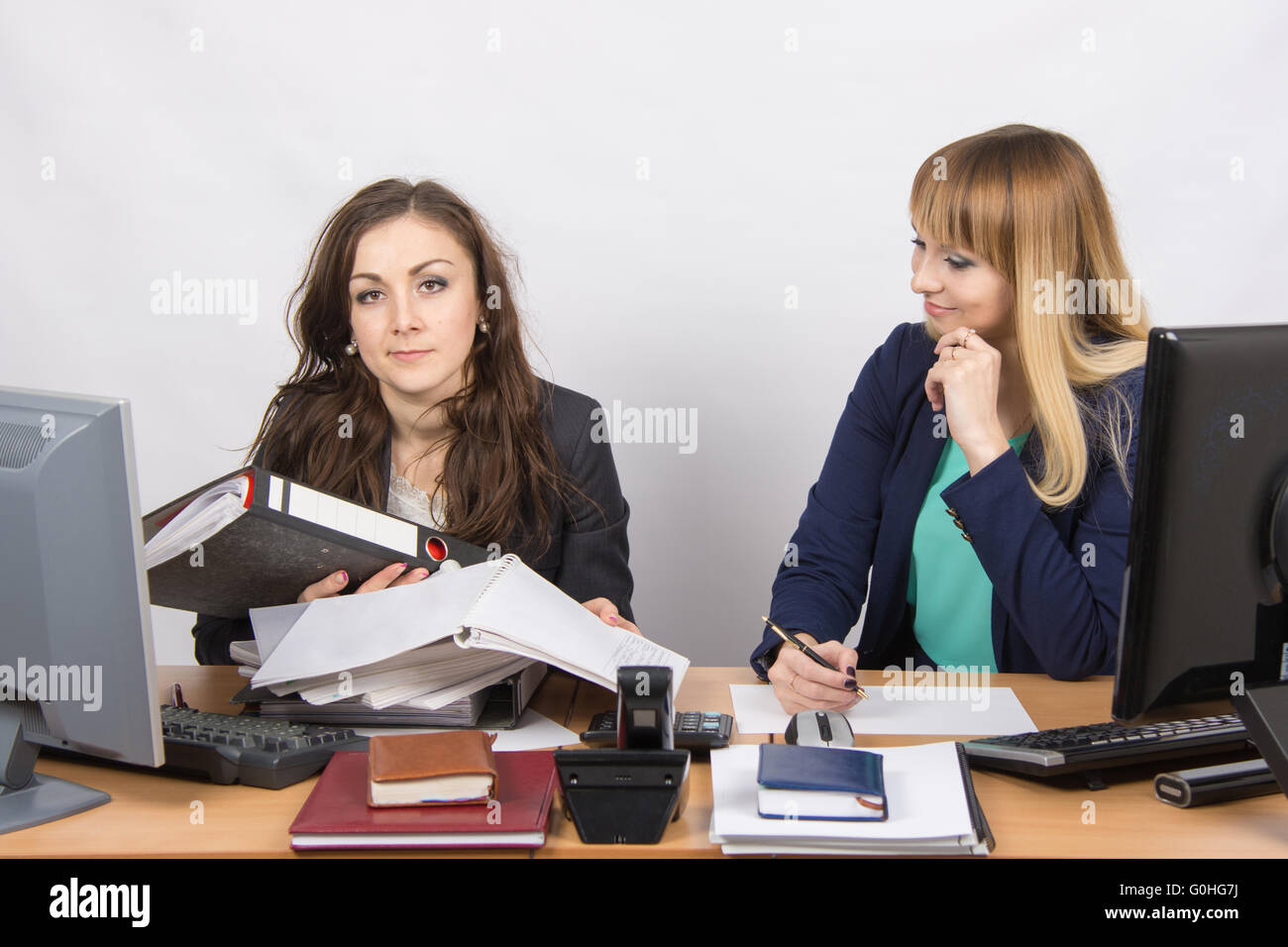 The situation in the office - one employee inundated with work and looking at the frame, the other does nothing, - Stock Image