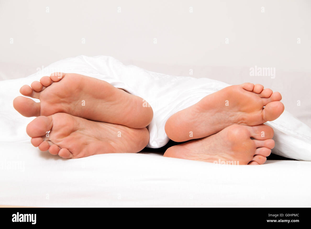 Feet of one couple in bed. Separation and divorce Stock Photo