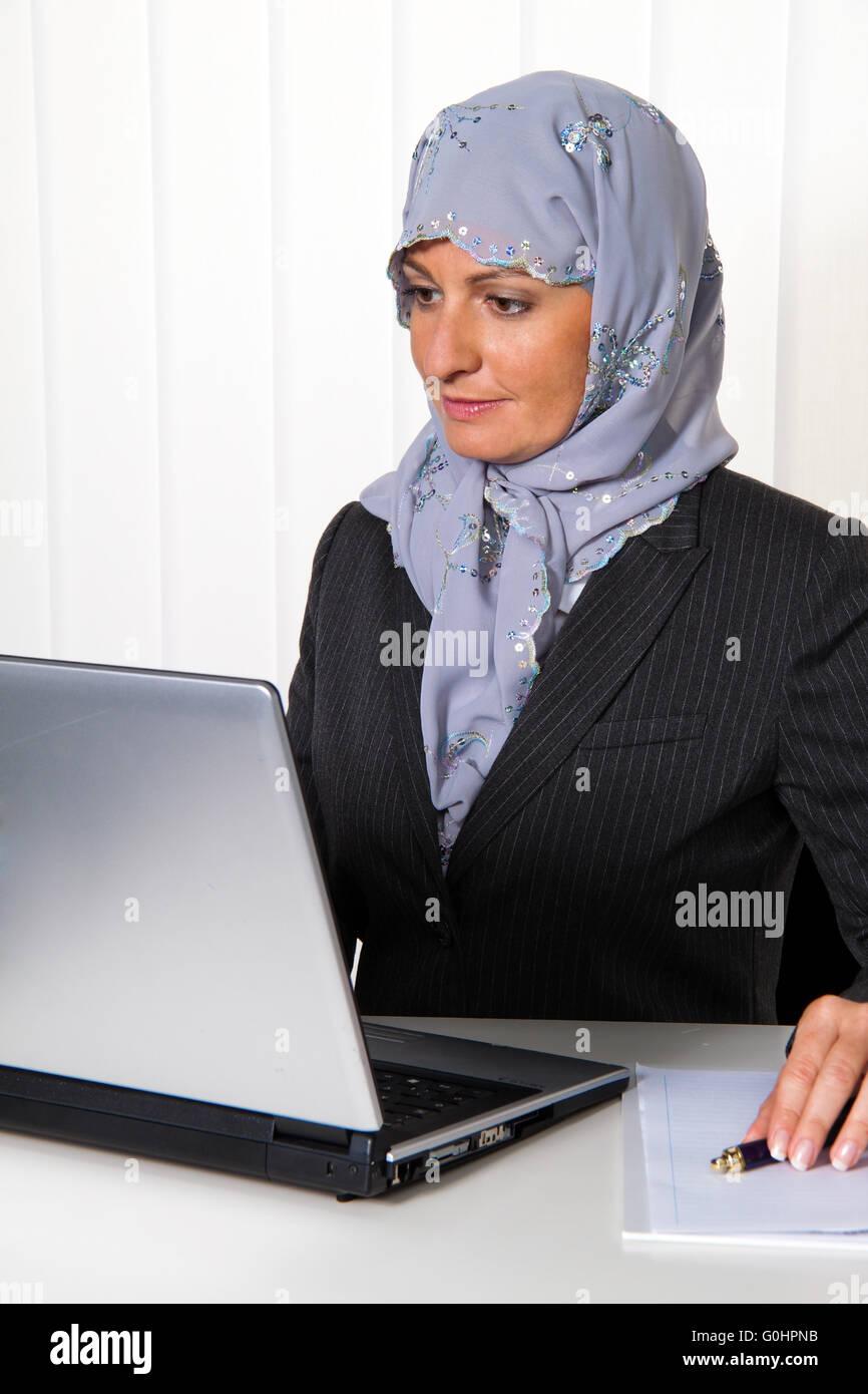 Symbolfoto Islam. Muslim woman wearing a headscarf at work - Stock Image
