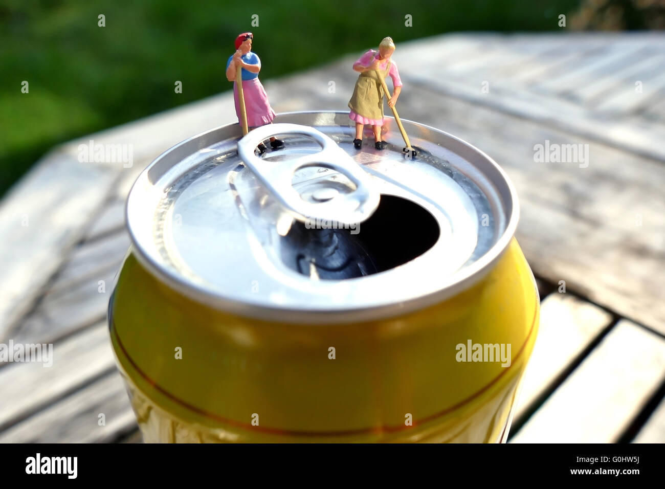 Miniature cleaning women sweeping on top of soda can with blurred background. Business concept Stock Photo