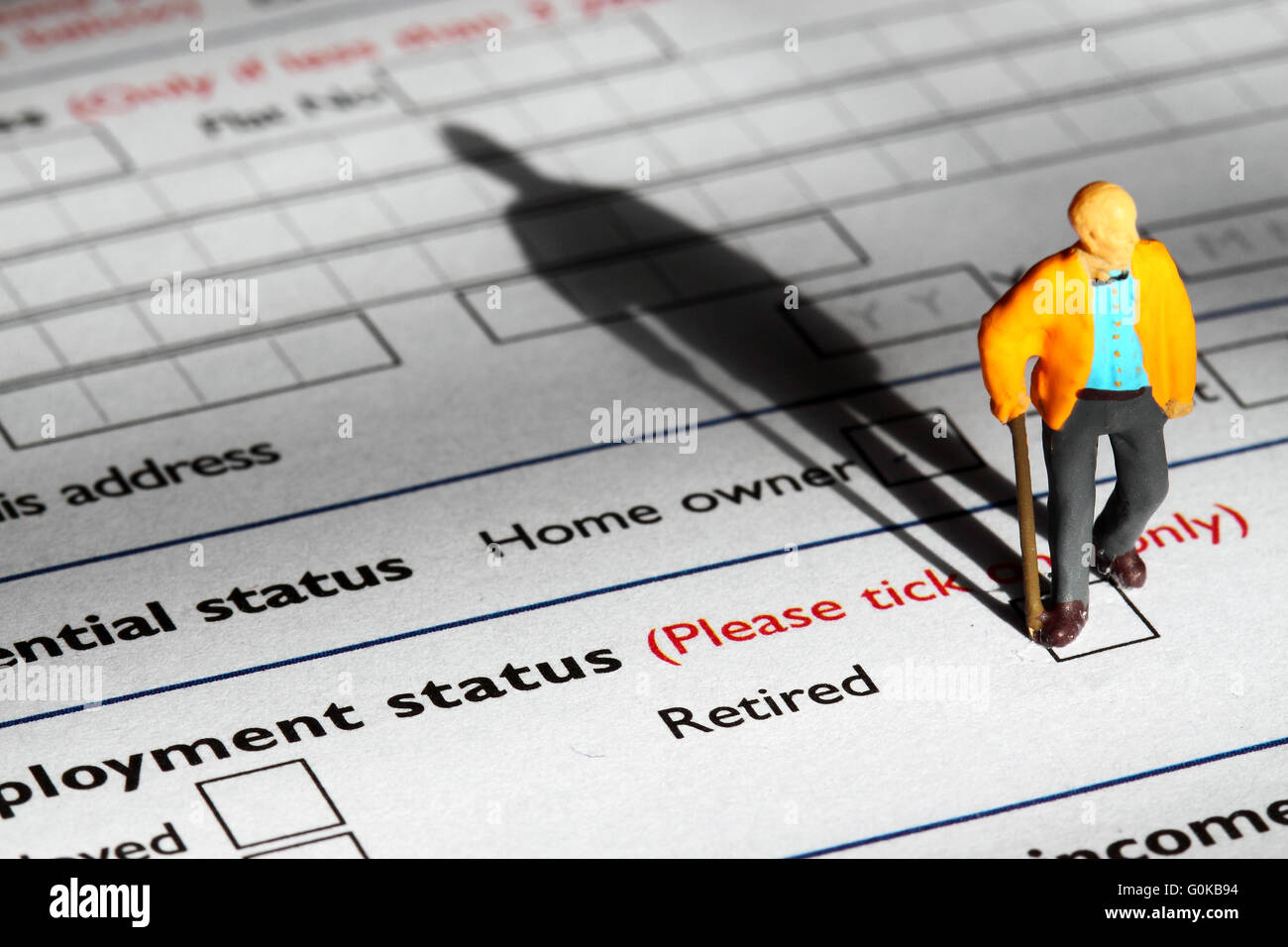 Miniature model pensioner standing on an application form - Stock Image