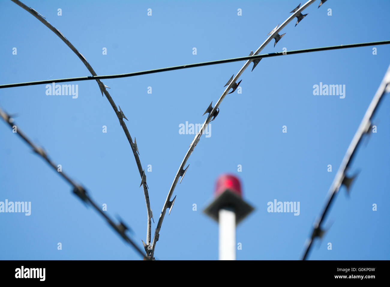 barbed wire and emergency light against the blue sky, selected focus, narrow depth of field - Stock Image
