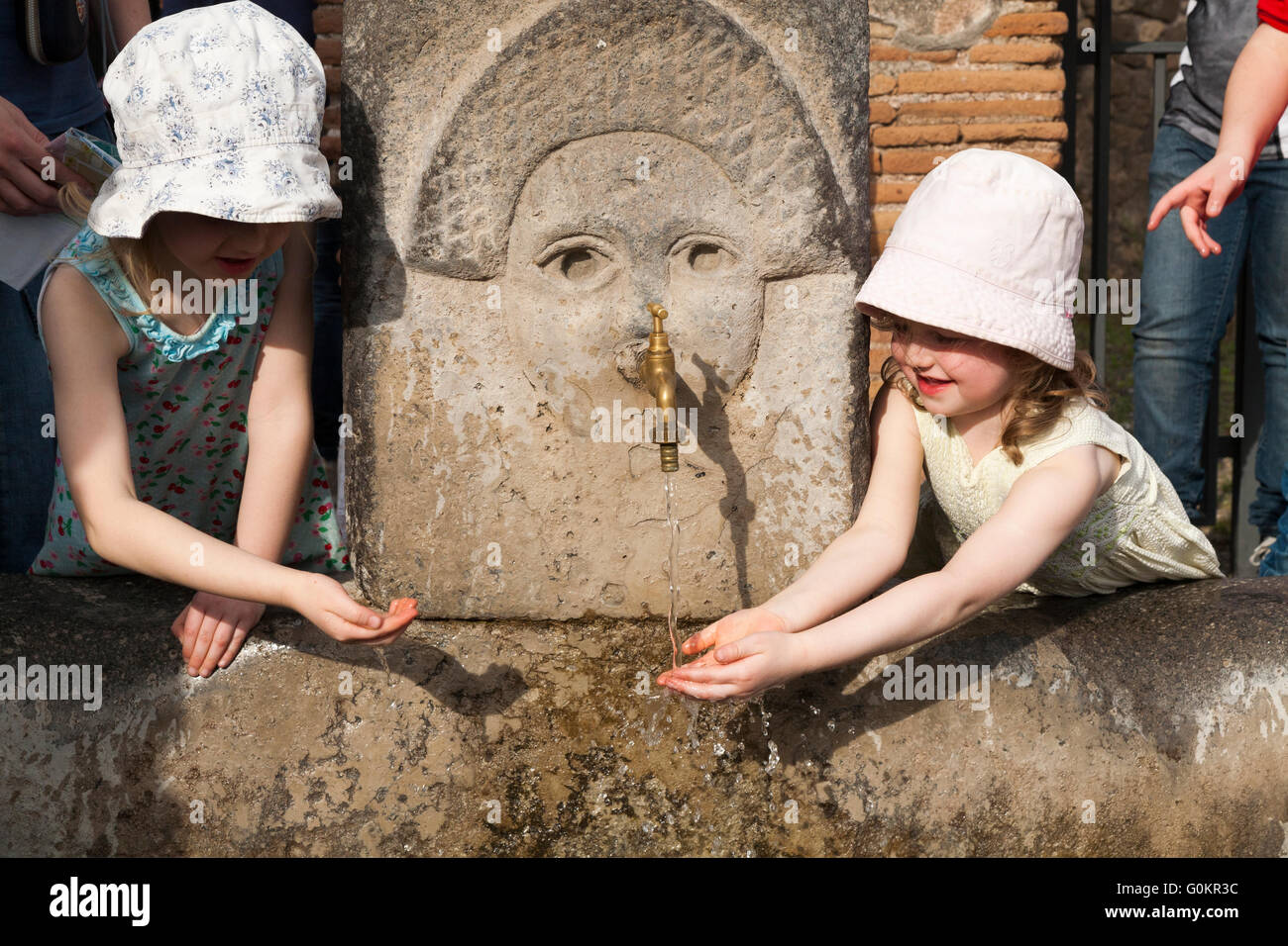 Tourist tourists child children kid kids drink / drinking from a public water fountain tap in Roman Pompeii Pompei. - Stock Image