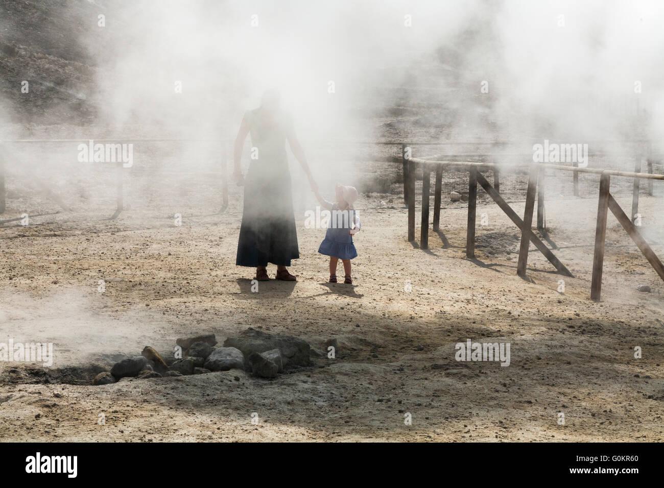 Tourist woman & child / family at Solfatara volcano steam & sulfurous fumes Pozzuoli, Naples Italy; Campi - Stock Image