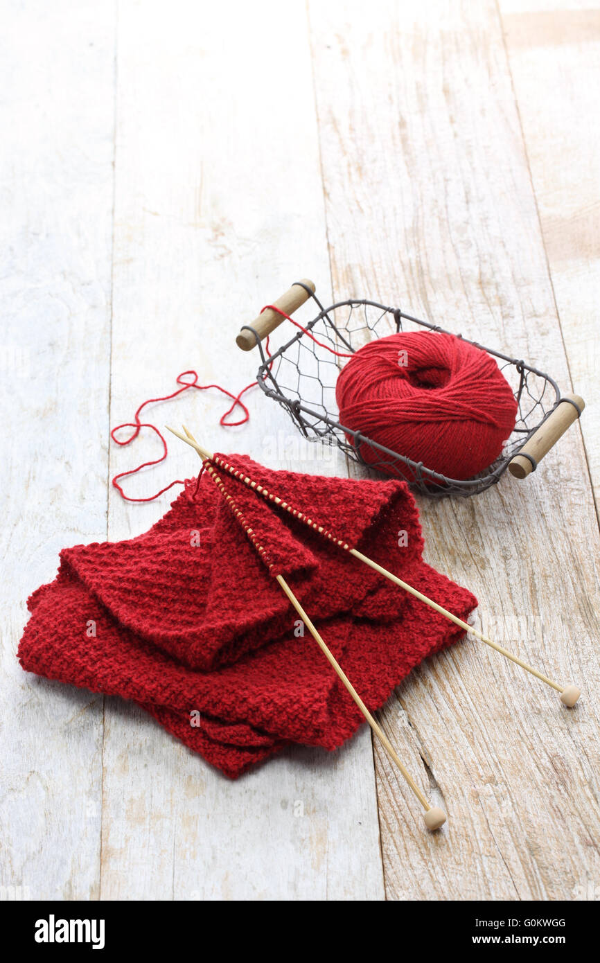 hand knitted red scarf, yarn ball and knitting needles, handmade christmas present - Stock Image