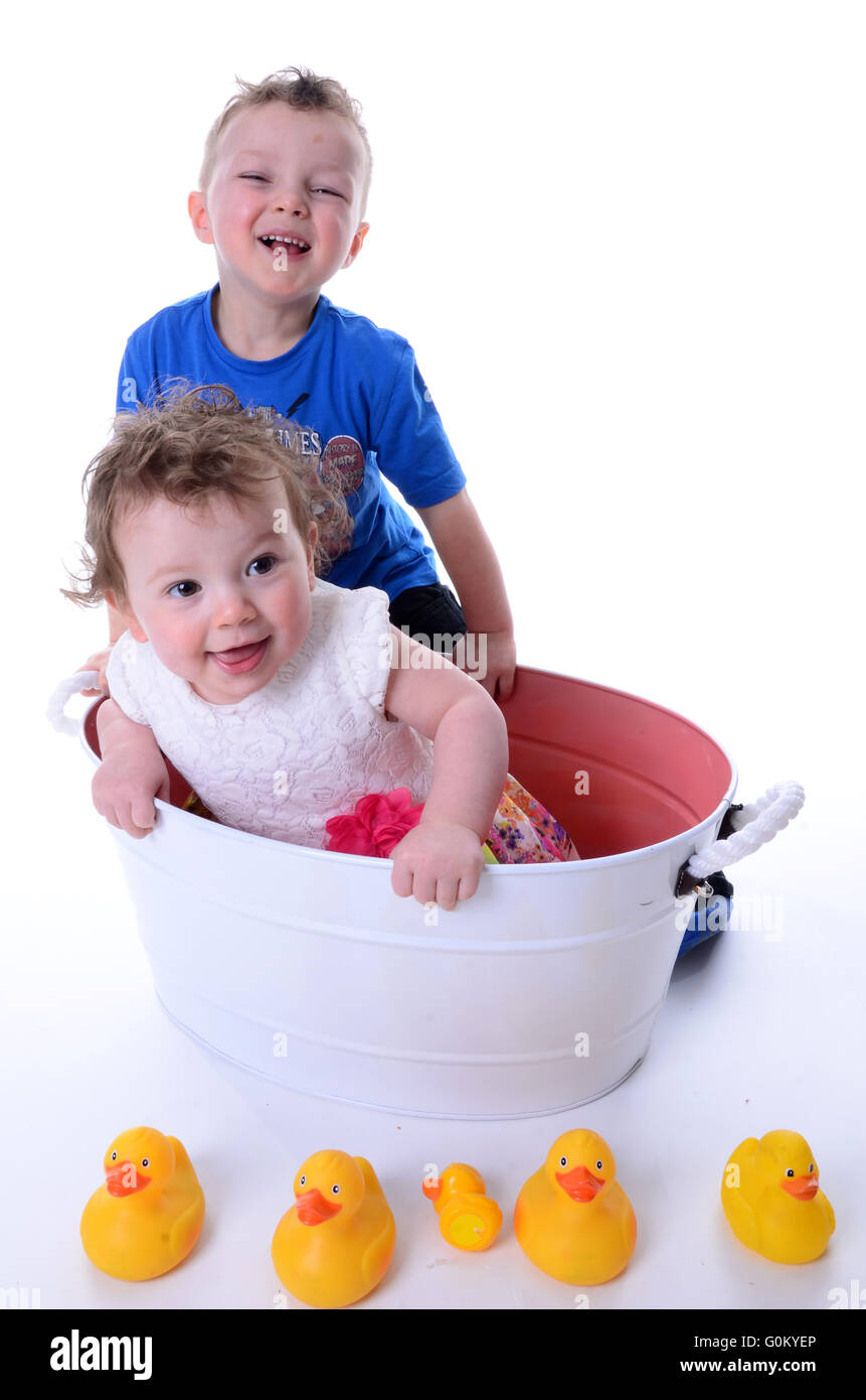 brother and sister playing in vintage bath tub - Stock Image