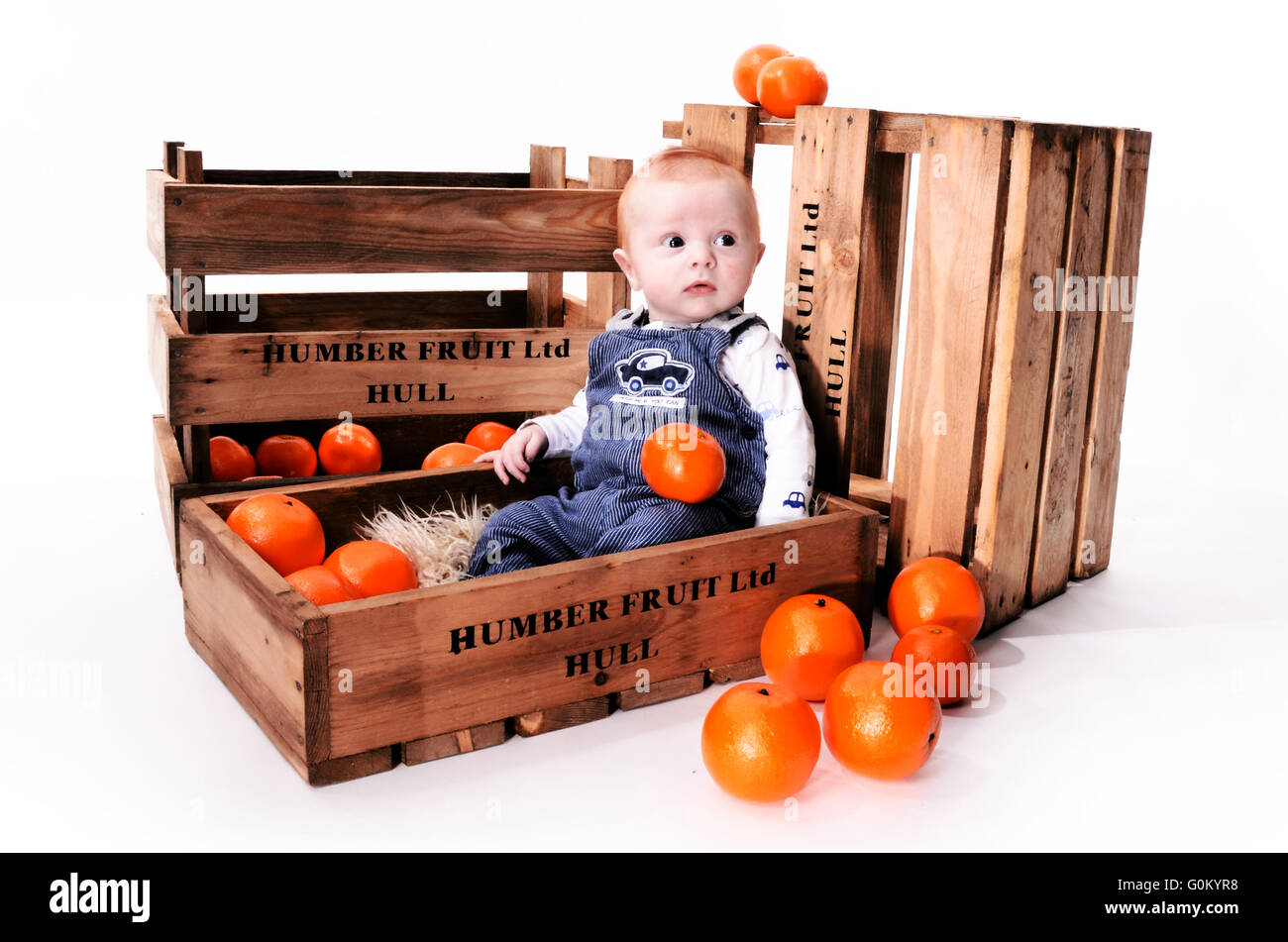baby sitting in fruit box, humber street fruit market. Kingston upon Hull, City of culture 2017, Hull Stock Photo