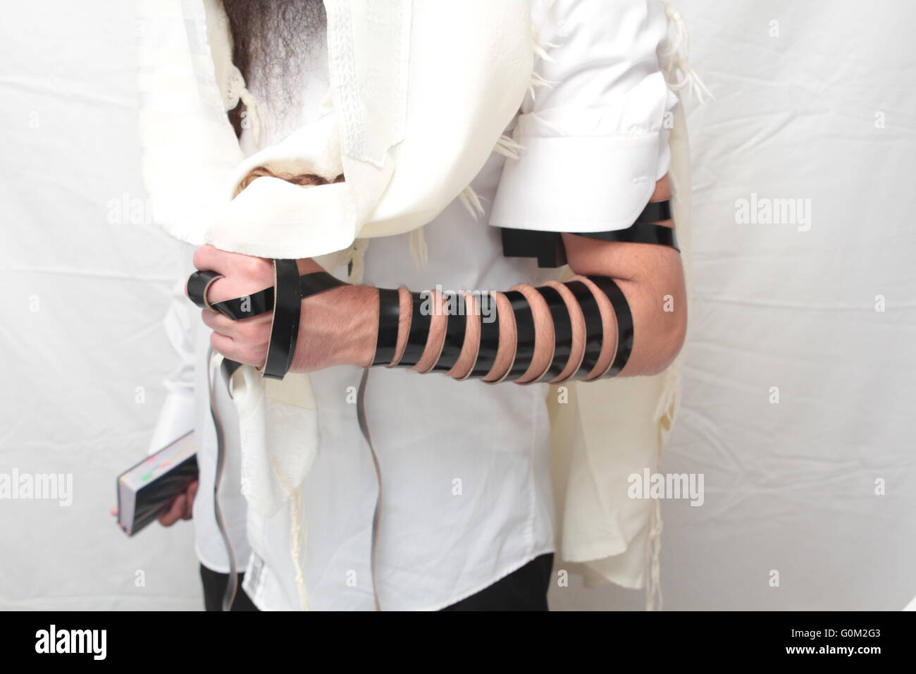 Jewish Man wrapped in tefillin pray . A religious orthodox Jew with arm-tefillin on his left hand prays - Stock Image