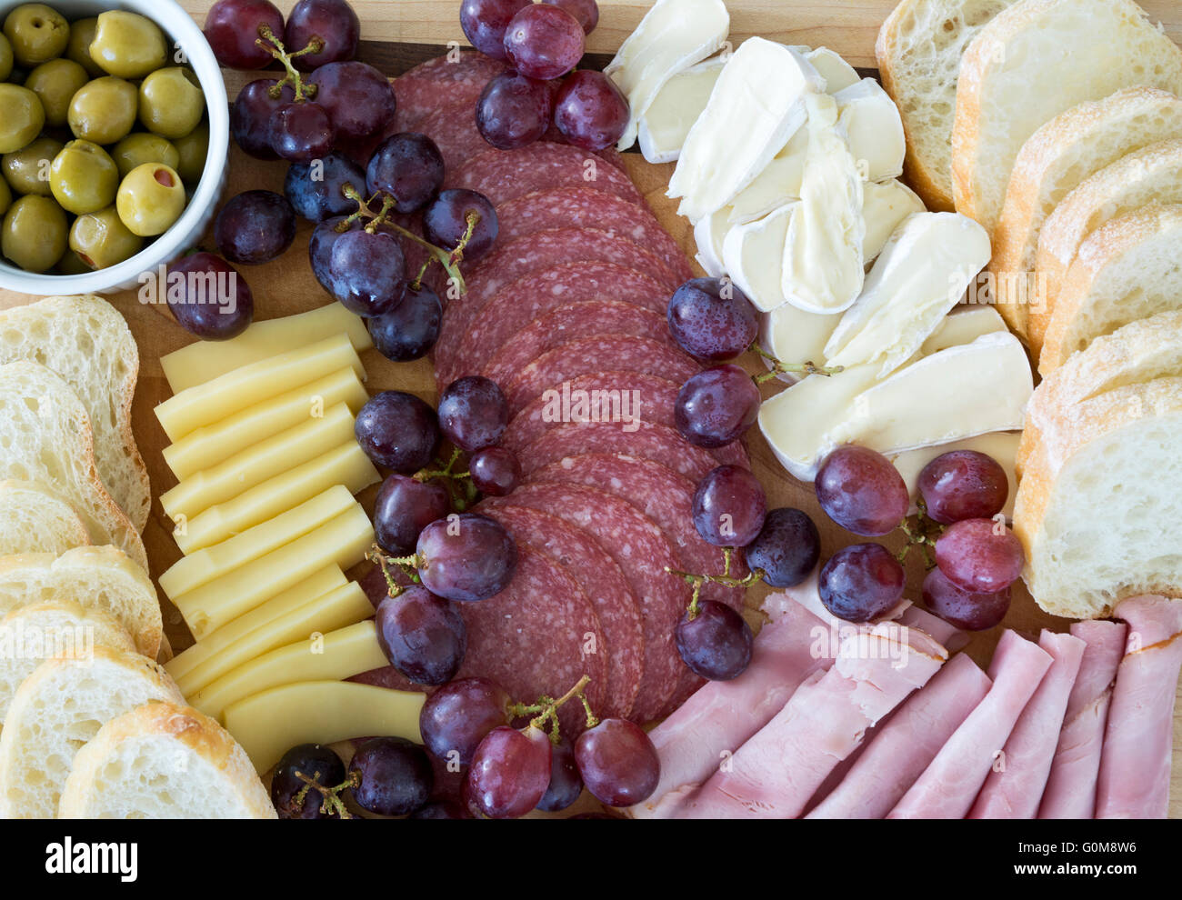 Charcuterie platter with meats, cheeses, bread and olives.  Meat and cheese deli platter with grapes and olives. - Stock Image