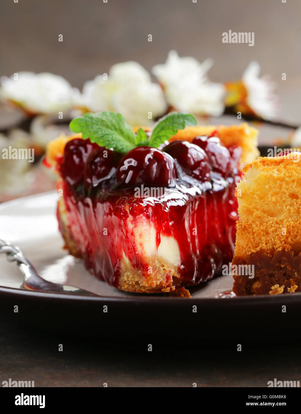 piece of cherry cheesecake and leaves of fresh mint - Stock Image
