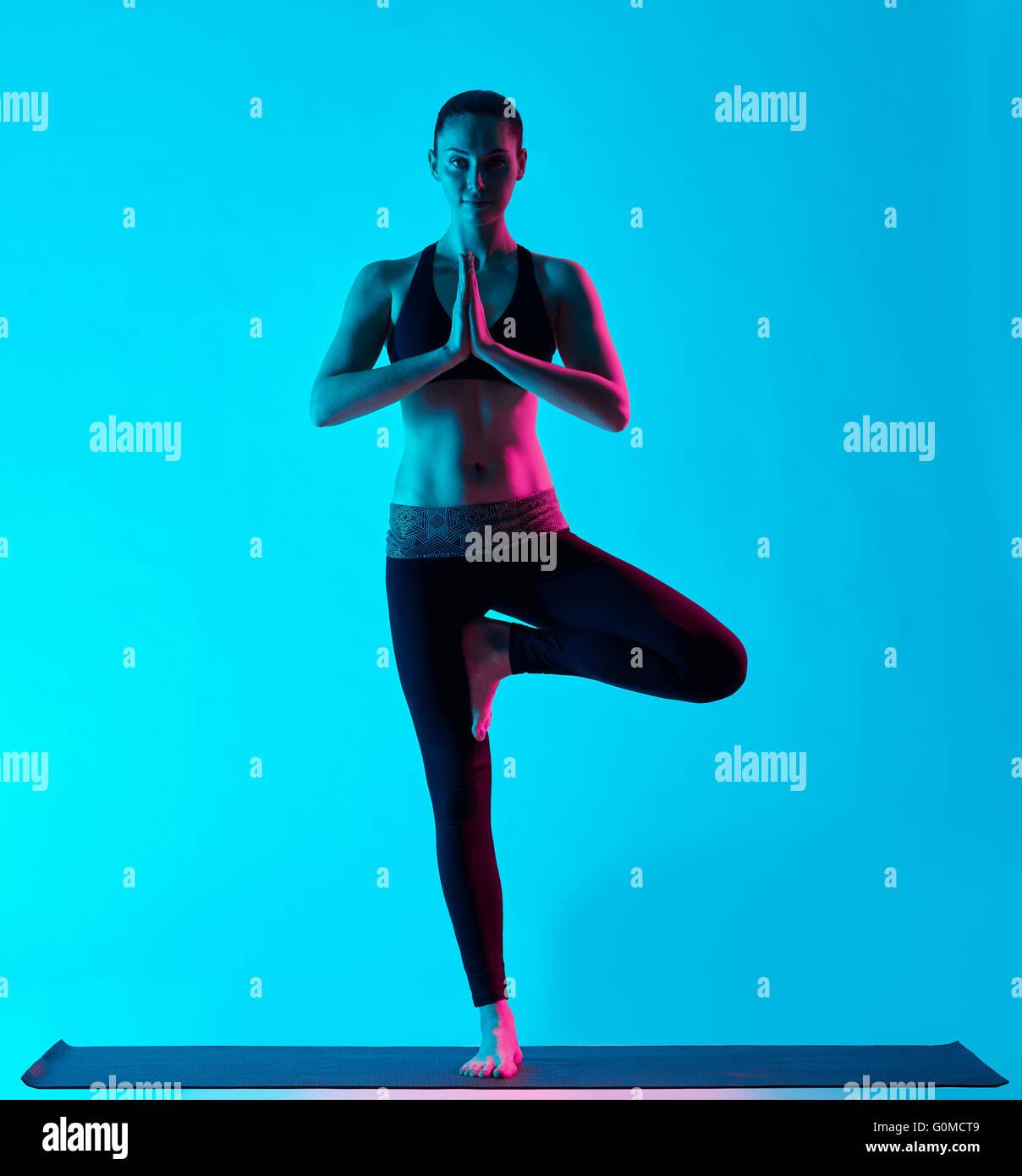 one caucasian woman exercising tree pose Vriksasana yoga exercices  in silhouette studio isolated on blue background Stock Photo