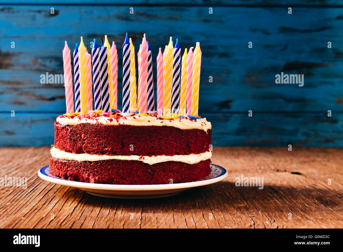 a red velvet cake topped with some unlit candles on a rustic wooden table - Stock Image