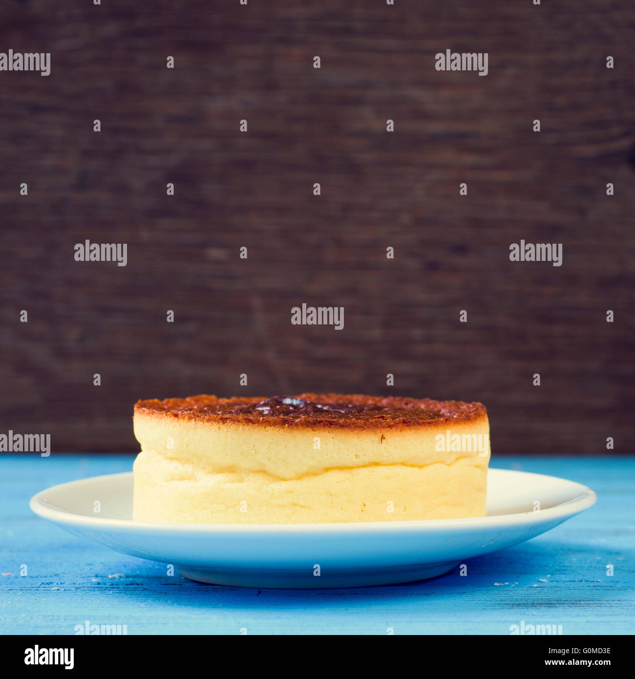 closeup of a cheesecake on a rustic blue wooden table, against a rustic wooden background - Stock Image