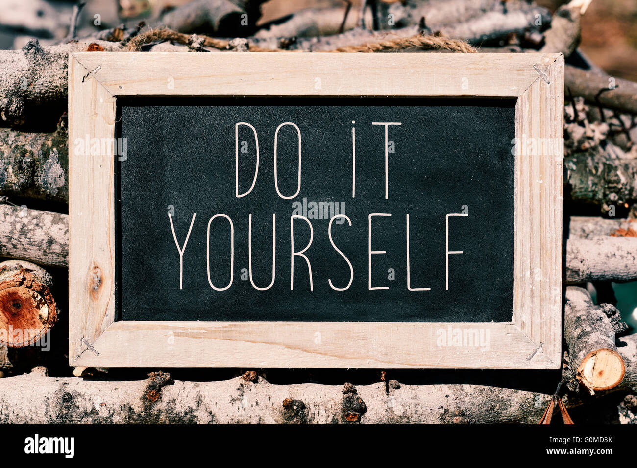 an aged chalkboard with the text do it yourself, placed on a pile of logs - Stock Image