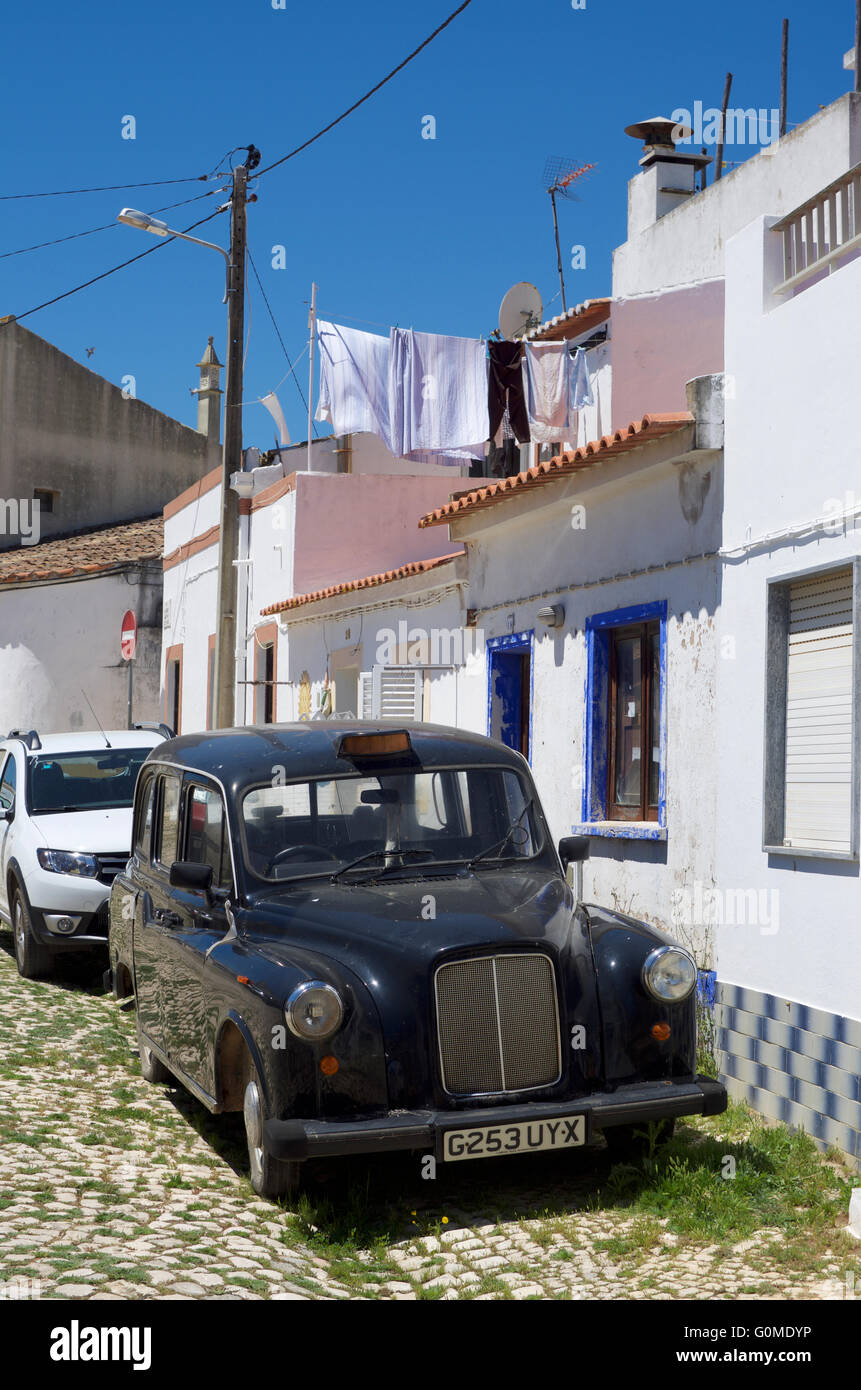 British black taxi cab parked in an Algarve village - Stock Image