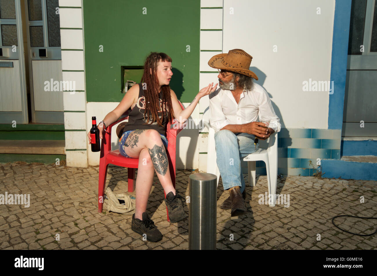 Tattooed foreign hippie girl talking to local man, Barao de Sao Joao Algarve Portugal - Stock Image