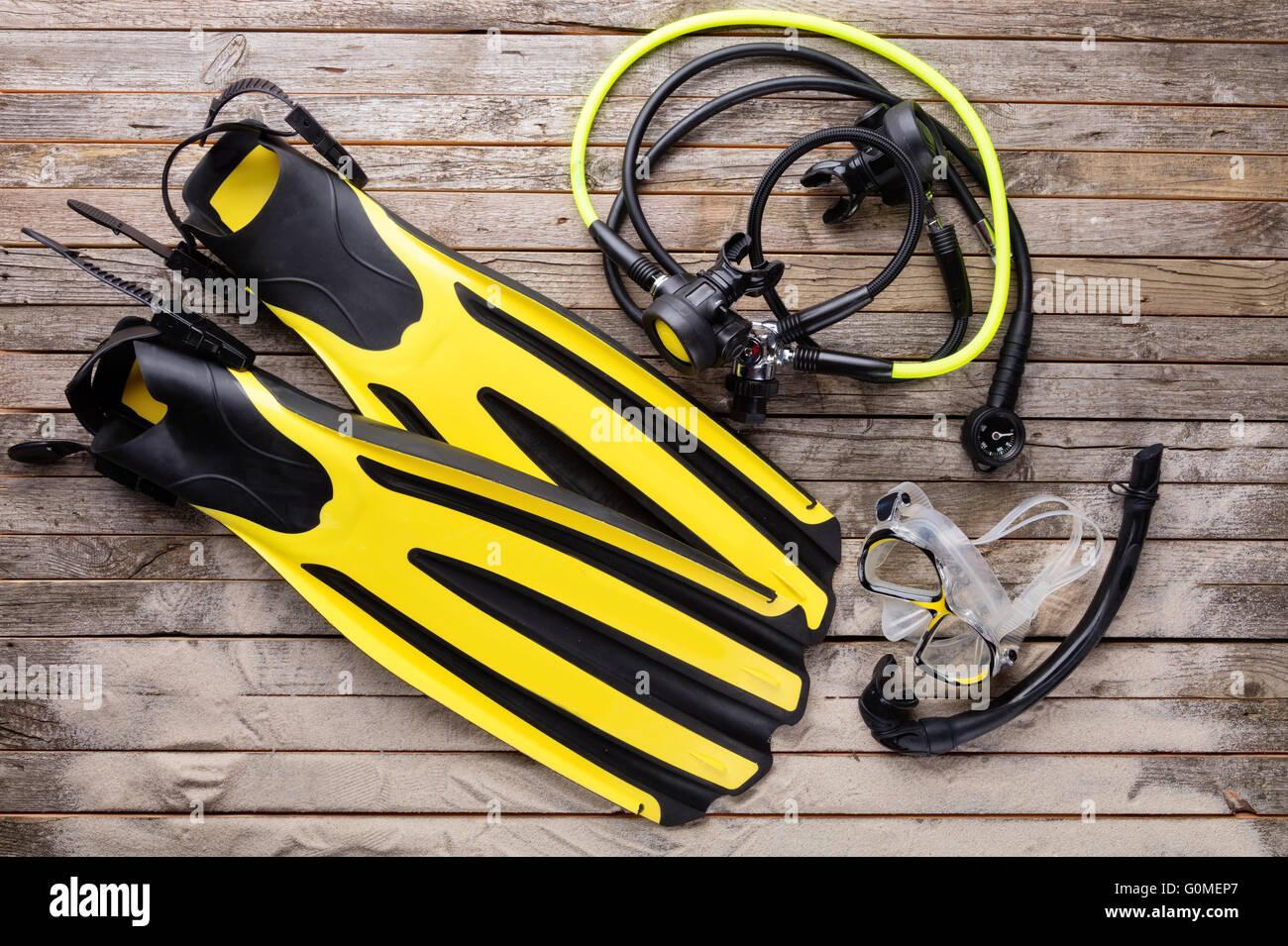 Mask, fins, regulator and snorkel on wooden desk. Equipment for diving - Stock Image