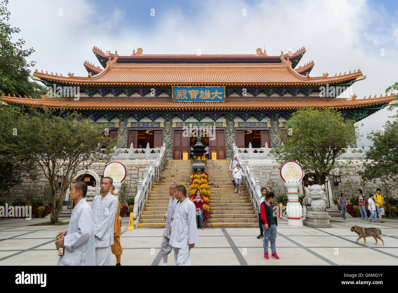 Monks and tourists in front of the Main Shrine Hall of Buddha at the Po Lin Monastery on Lantau Island in Hong Kong, - Stock Image