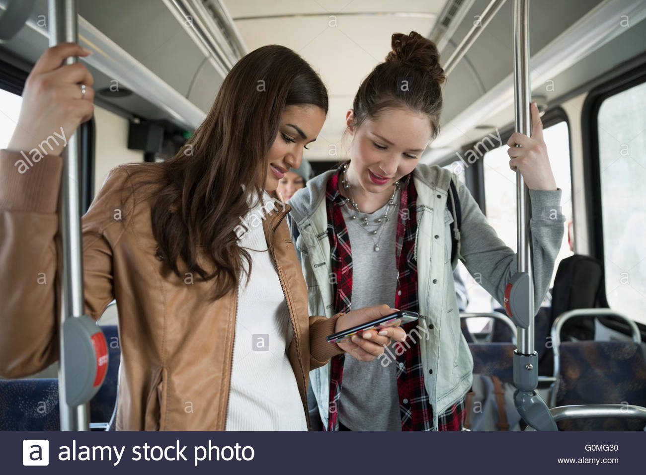 Teenage girls using cell phone standing on bus - Stock Image