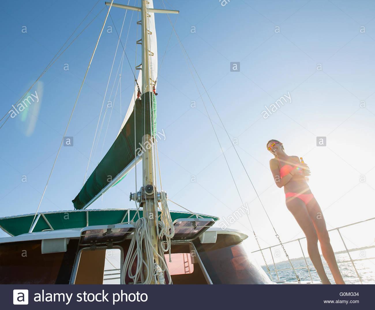 Woman in bikini on yacht under sunny blue sky - Stock Image