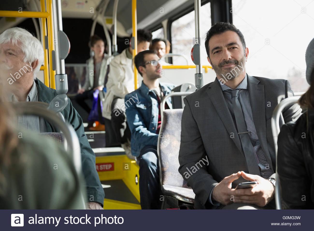 Portrait confident businessman riding bus - Stock Image