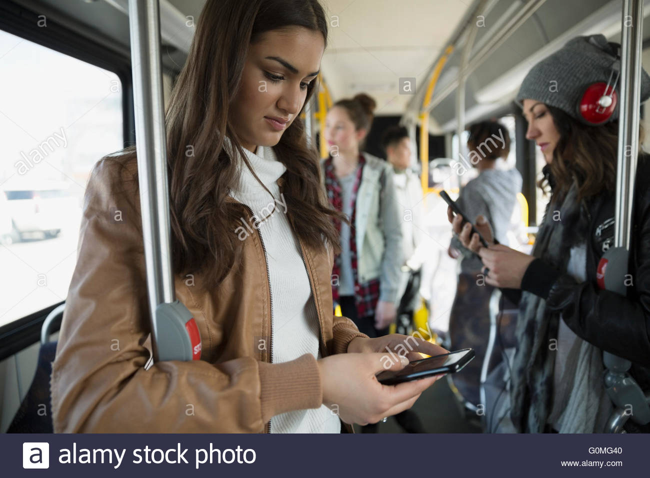 Teenage girl texting cell phone standing on bus - Stock Image