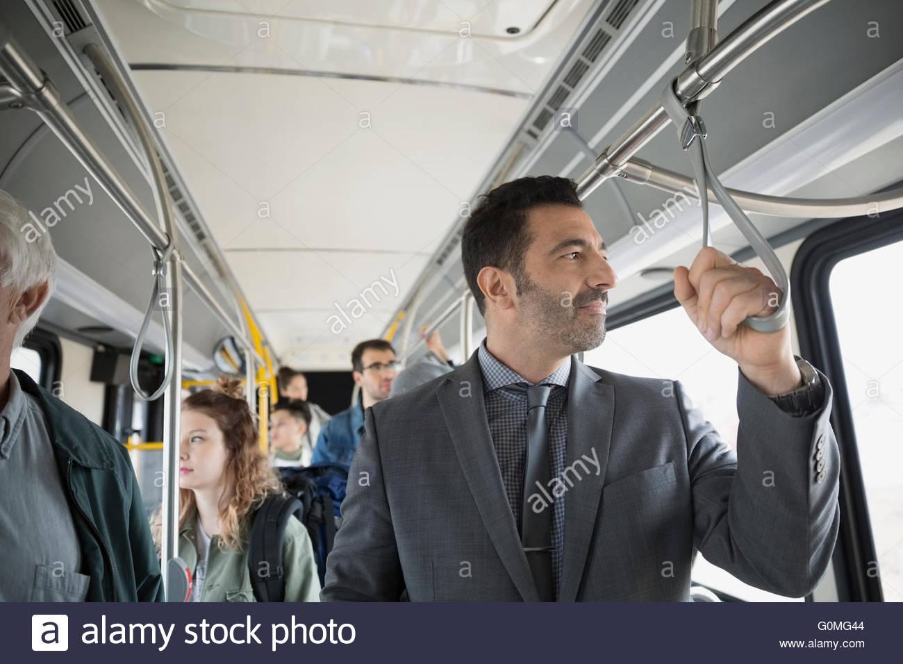 Businessman standing riding bus - Stock Image
