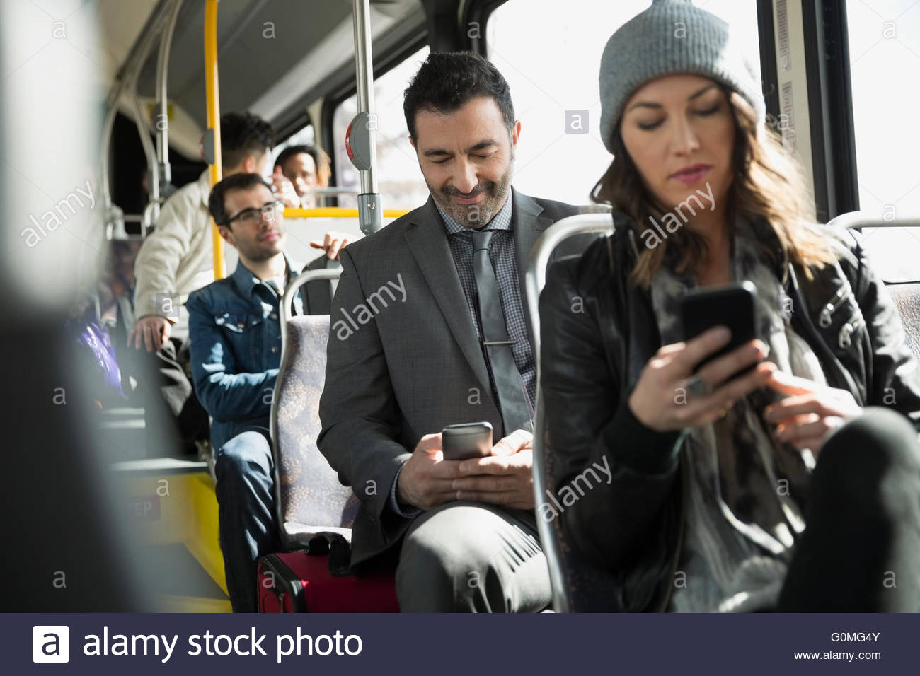 People using cell phones on bus - Stock Image