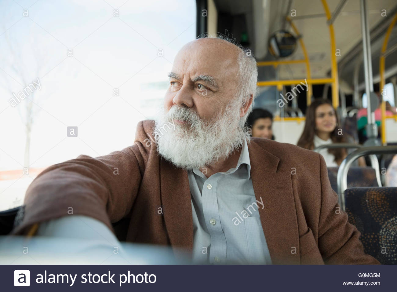 Pensive senior man riding bus looking out window - Stock Image