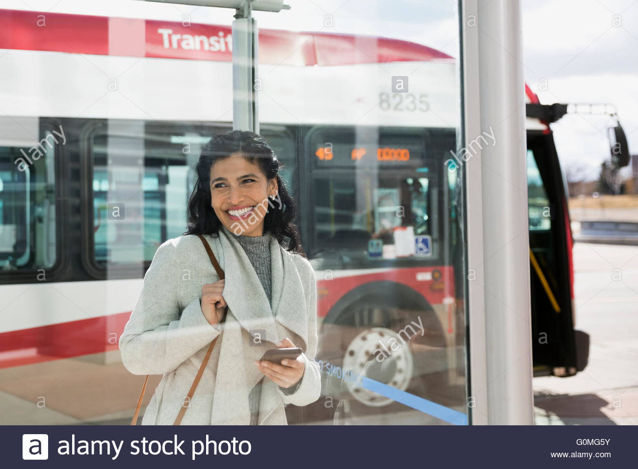 Smiling woman waiting at bus stop - Stock Image