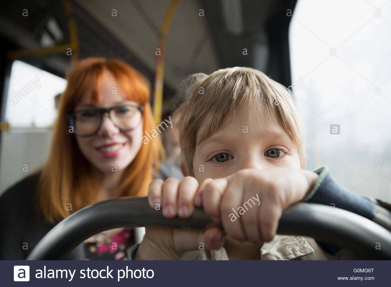 Portrait curious boy riding bus with mother - Stock Image