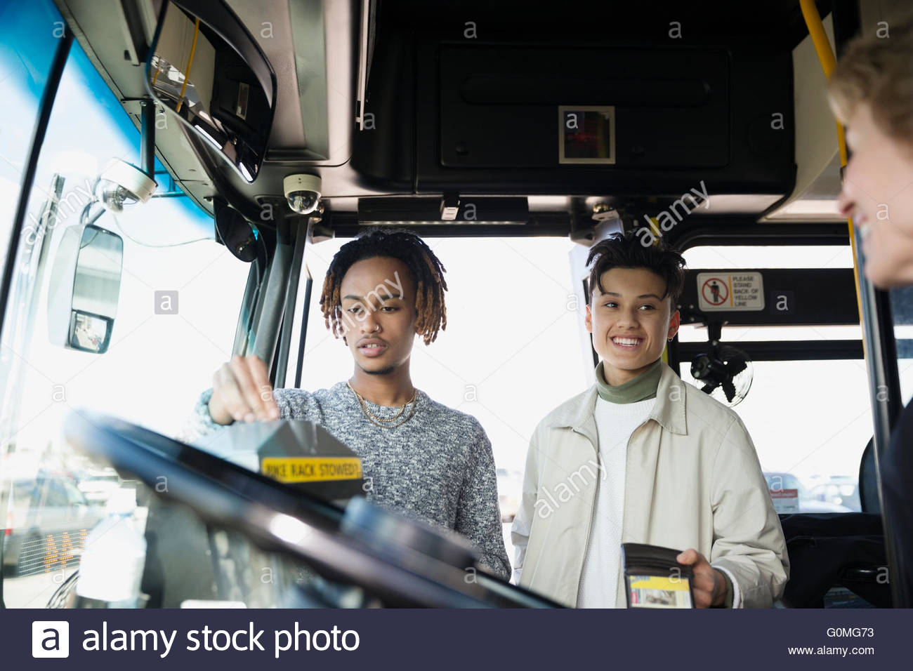 Young men boarding bus giving ticket to driver - Stock Image