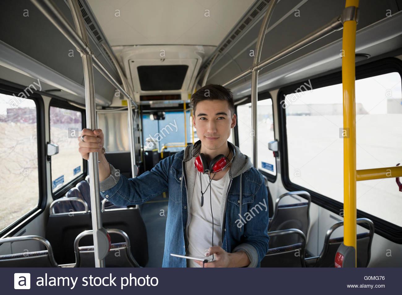 Portrait confident young man headphones digital tablet bus - Stock Image