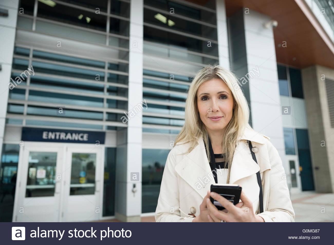 Portrait confident businesswoman cell phone outside train station - Stock Image