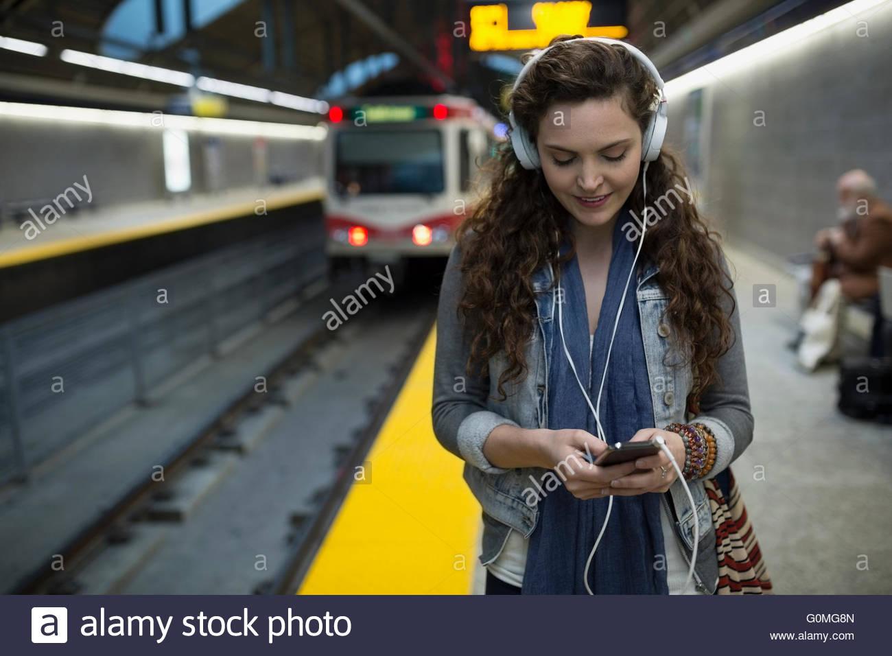 Young woman listening music headphones subway station platform - Stock Image