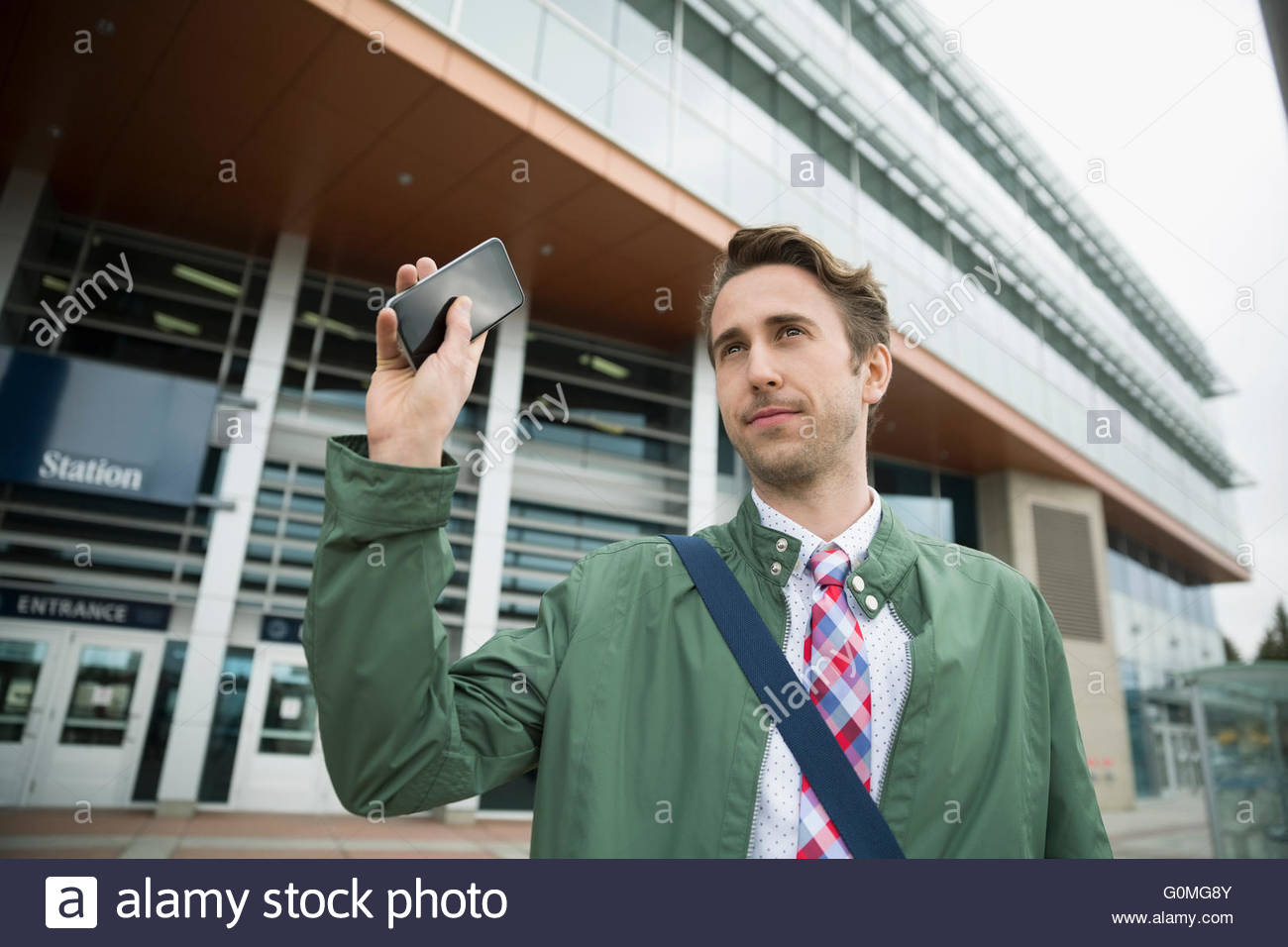 Businessman with cell phone waving outside train station - Stock Image